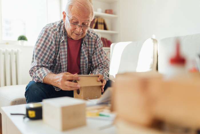 Senior man and grandfather embracing aging and enjoying his golden years while exploring his hobby of wood working and making bird houses while living at Jackson Creek senior living community